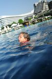 Child swimming in pool. Close up of female child swimming in pool with resort buildings in background stock photo