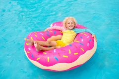 Child in swimming pool on donut float. Child in swimming pool on funny inflatable donut float ring. Little boy learning to swim in outdoor pool of tropical stock photography