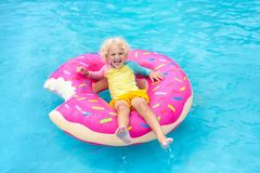 Child in swimming pool on donut float. Child in swimming pool on funny inflatable donut float ring. Little boy learning to swim in outdoor pool of tropical stock photo