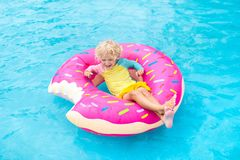 Child in swimming pool on donut float. Child in swimming pool on funny inflatable donut float ring. Little boy learning to swim in outdoor pool of tropical royalty free stock photo