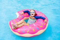 Child in swimming pool on donut float Stock Photography