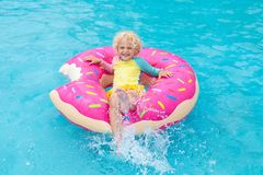 Child in swimming pool on donut float. Child in swimming pool on funny inflatable donut float ring. Little boy learning to swim in outdoor pool of tropical stock photos