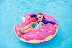 Child in swimming pool on donut float. Child in swimming pool on funny inflatable donut float ring. Little girl learning to swim in outdoor pool of tropical royalty free stock photo