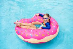 Child in swimming pool on donut float. Child in swimming pool on funny inflatable donut float ring. Little girl learning to swim in outdoor pool of tropical stock photography