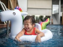 Child in swimming pool. Funny little girl swims in a pool in an white life preserver. Children play outdoors in summer.  stock image