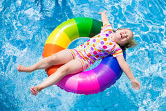 Child in swimming pool. Happy little girl playing with colorful inflatable ring in outdoor swimming pool on hot summer day. Kids learn to swim. Children wearing Royalty Free Stock Images