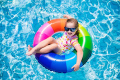 Child in swimming pool. Happy little girl playing with colorful inflatable ring in outdoor swimming pool on hot summer day. Kids learn to swim. Children wearing Stock Image