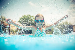 Child in swimming pool. Child having fun in swimming pool. Kid playing outdoors. Summer vacation and healthy lifestyle concept Stock Photos