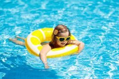 Child in swimming pool on ring toy. Kids swim royalty free stock photography