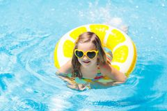 Child in swimming pool on ring toy. Kids swim stock images