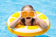 Child in swimming pool. Kid eating orange. Little girl in swimming pool with inflatable toy ring eating orange. Kids swim on summer vacation. Tropical fruit and Stock Photography