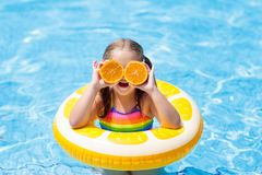 Child in swimming pool. Kid eating orange. Little girl in swimming pool with inflatable toy ring eating orange. Kids swim on summer vacation. Tropical fruit and Royalty Free Stock Image