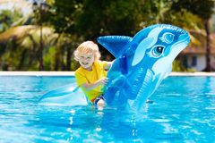 Child in swimming pool. Kid on inflatable float. Child playing in swimming pool. Kids learn to swim. Little baby boy with inflatable toy float playing in water royalty free stock images