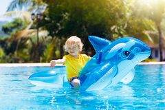 Child in swimming pool. Kid on inflatable float. Child playing in swimming pool. Kids learn to swim. Little baby boy with inflatable toy float playing in water royalty free stock photo