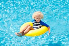 Child in swimming pool. Kids swim. Water play. Stock Images