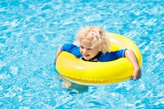Child in swimming pool. Kids swim. Water play. Child with goggles in swimming pool. Little boy learning to swim and dive in outdoor pool of tropical resort stock images