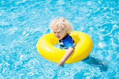 Child in swimming pool. Kids swim. Water play. Child with goggles in swimming pool. Little boy learning to swim and dive in outdoor pool of tropical resort stock photo