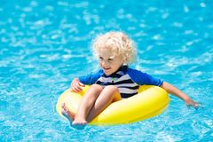 Child in swimming pool. Kids swim. Water play. Child with goggles in swimming pool. Little boy learning to swim and dive in outdoor pool of tropical resort stock photos