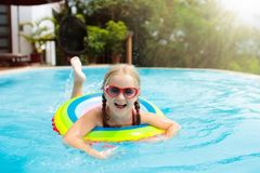 Child in swimming pool. Kids swim. Water play. Child with goggles in swimming pool. Little girl learning to swim and dive in outdoor pool of tropical resort stock photography