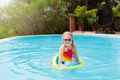 Child in swimming pool. Kids swim. Water play. Child with goggles in swimming pool. Little girl learning to swim and dive in outdoor pool of tropical resort stock image