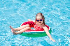 Child in swimming pool. Kids swim. Water play. Child with watermelon inflatable ring in swimming pool. Little girl learning to swim in outdoor pool of tropical royalty free stock image