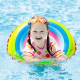 Child in swimming pool. Kids swim. Water play. Child with goggles in swimming pool. Little girl learning to swim and dive in outdoor pool of tropical resort stock photos