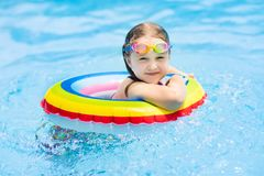 Child in swimming pool. Kids swim. Water play. Child with goggles in swimming pool. Little girl learning to swim and dive in outdoor pool of tropical resort royalty free stock photo