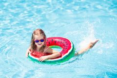 Child in swimming pool. Kids swim. Water play. Child with watermelon inflatable ring in swimming pool. Little girl learning to swim in outdoor pool of tropical stock photo