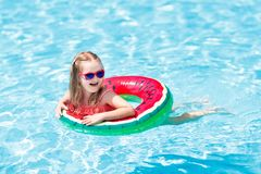 Child in swimming pool. Kids swim. Water play. Child with watermelon inflatable ring in swimming pool. Little girl learning to swim in outdoor pool of tropical stock images