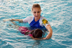 Child swimming pool lesson. GOLD COAST - OCT 15 2014:Swimming trainer during child (Talya Ben-Ari age 04) swimming pool lesson.Children who have an early Royalty Free Stock Photography