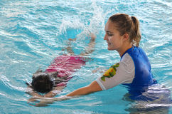 Child swimming pool lesson. GOLD COAST - OCT 15 2014:Swimming trainer during child (Talya Ben-Ari age 04) swimming pool lesson.Children who have an early Royalty Free Stock Images