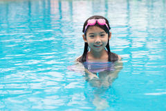Child in swimming pool. Little Asian girl smiling and posing in swimming pool Royalty Free Stock Photos
