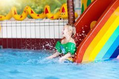 Child on swimming pool slide. Kids swim. Water fun. Child on swimming pool slide. Kid having fun sliding in water amusement park. Kids swim. Family summer Royalty Free Stock Photo