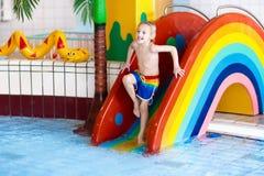 Child on swimming pool slide. Kids swim. Water fun. Child on swimming pool slide. Kid having fun sliding in water amusement park. Kids swim. Family summer Stock Images