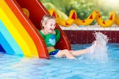 Child on swimming pool slide. Kids swim. Water fun. Child on swimming pool slide. Kid having fun sliding in water amusement park. Kids swim. Family summer Royalty Free Stock Photography