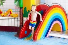 Child on swimming pool slide. Kids swim. Water fun. Child on swimming pool slide. Kid having fun sliding in water amusement park. Kids swim. Family summer stock photos
