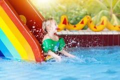 Child on swimming pool slide. Kids swim. Water fun. Child on swimming pool slide. Kid having fun sliding in water amusement park. Kids swim. Family summer Royalty Free Stock Image