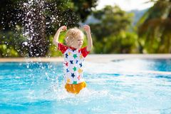 Child in swimming pool. Summer vacation with kids. Child playing in swimming pool. Summer vacation with kids. Little boy jumping into water during exotic royalty free stock photography