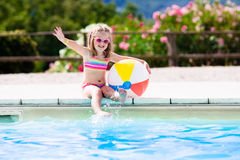 Child in swimming pool on summer vacation. Little girl playing ball in outdoor swimming pool jumping into water on summer vacation on tropical beach island Stock Images