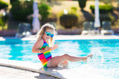 Child in swimming pool on summer vacation. Little girl playing in outdoor swimming pool jumping into water on summer vacation on tropical beach island. Child Stock Image