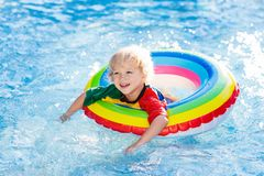 Child in swimming pool on toy ring. Kids swim royalty free stock photo