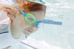 Child Swimming in Pool Underwater Stock Photo