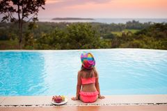 Child at swimming pool at sunset. Kid at sea. Child at swimming pool watching sunset at sea shore. Little girl looking at ocean relaxing at infinity pool of stock images