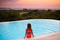 Child at swimming pool at sunset. Kid at sea. Child at swimming pool watching sunset at sea shore. Little girl looking at ocean relaxing at infinity pool of royalty free stock photography