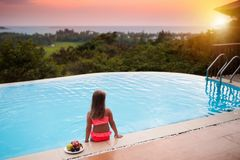 Child at swimming pool at sunset. Kid at sea. Child at swimming pool watching sunset at sea shore. Little girl looking at ocean relaxing at infinity pool of royalty free stock photos