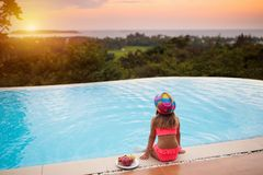 Child at swimming pool at sunset. Kid at sea. Child at swimming pool watching sunset at sea shore. Little girl looking at ocean relaxing at infinity pool of stock photo