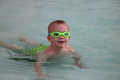 Child swimming in pool. A young boy enjoys a swim in a swimming pool Royalty Free Stock Image