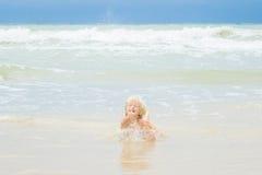 A happy blond boy lies in a water on a beach, Vietnam, Nha-trang stock photos