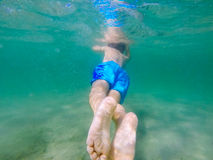 Child swimming seen from behind Stock Photo