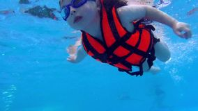 Child swimming under water slow motion. Children in life jacket swims underwater stock footage